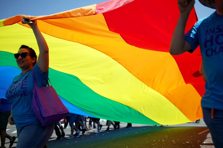 Marchers carry a rainbow flag in the LA Pride Parade on June 8, 2014 in West Hollywood, California.