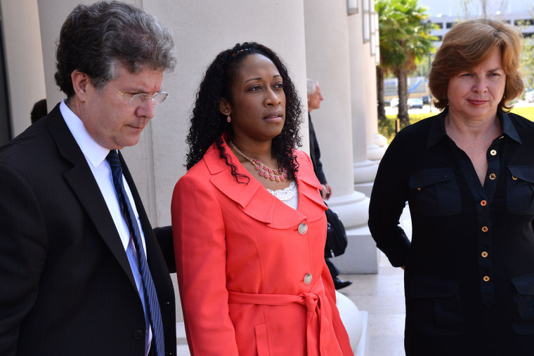 Defense co-counsel Bruce Zimet, left, and Faith Gay, right, stand with Marissa Alexander as they speak to the media, June 10, 2014 in Jacksonville, Fla.