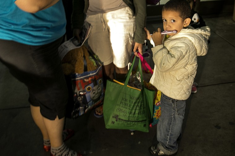 In this photo taken July 1, 2014, three-year-old Josefa, of Honduras, stands next to his mother, Eide Cerrato, center, as they prepare to board a bus leaving the city bus station in McAllen, Texas.