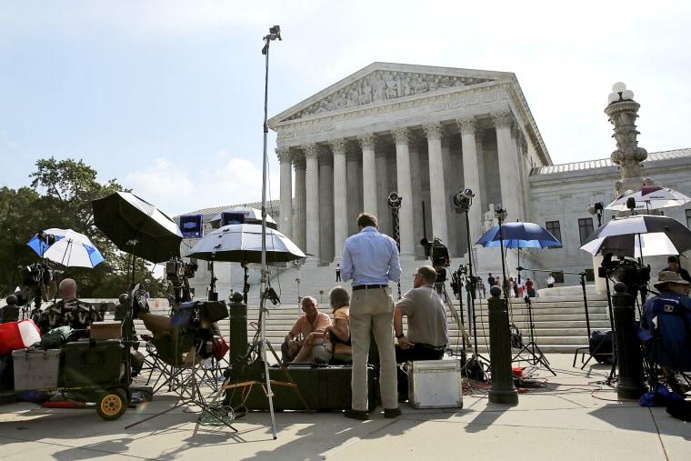 Numerous news crews await outside the Supreme Court in Washington June 25, 2014.