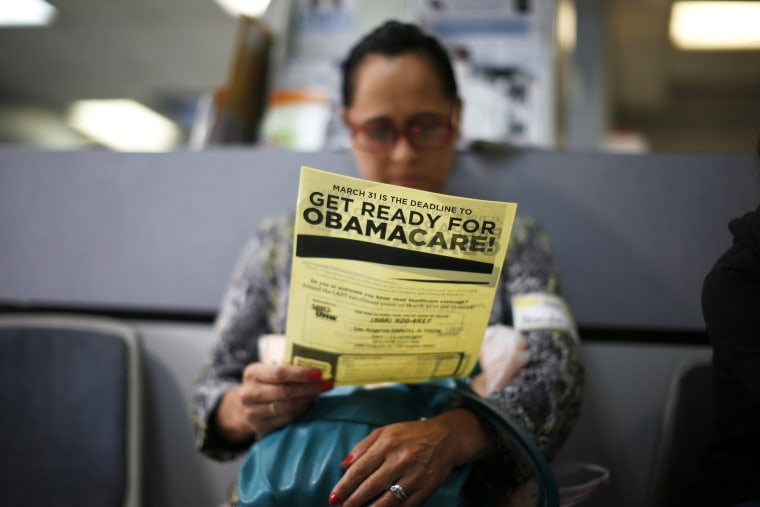 A woman reads a leaflet at a health insurance enrollment event in Cudahy, California March 27, 2014.