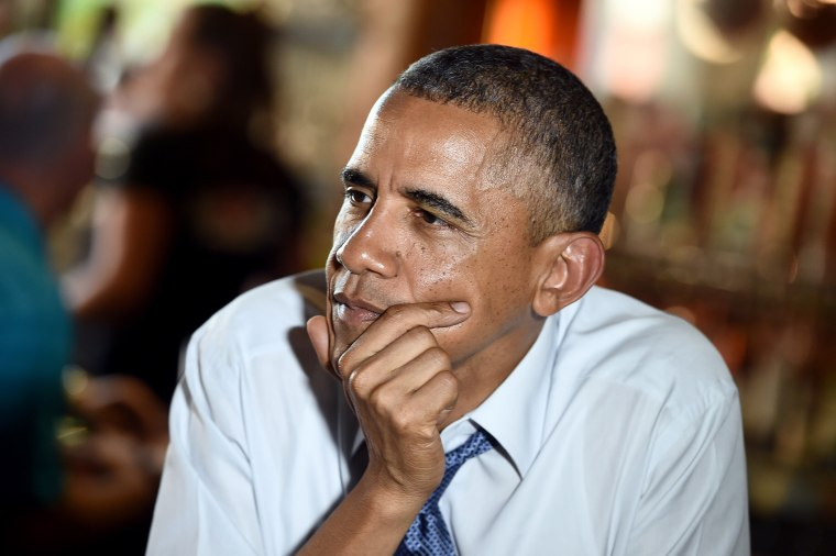 US President Barack Obama listens to a group of people, who wrote letters to him, as he sits to dine with them at a restaurant in Denver, Colorado, on July 8, 2014.