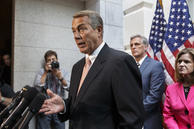 John Boehner talks with reporters on Capitol Hill in Washington, Wednesday, July 23, 2014, following a Republican strategy session.