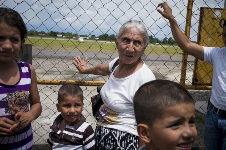 A family waits for a plane of migrants deported from the United States, arriving at Ramon Villeda Morales Airport in San Pedro Sula, Honduras, July 14, 2014.