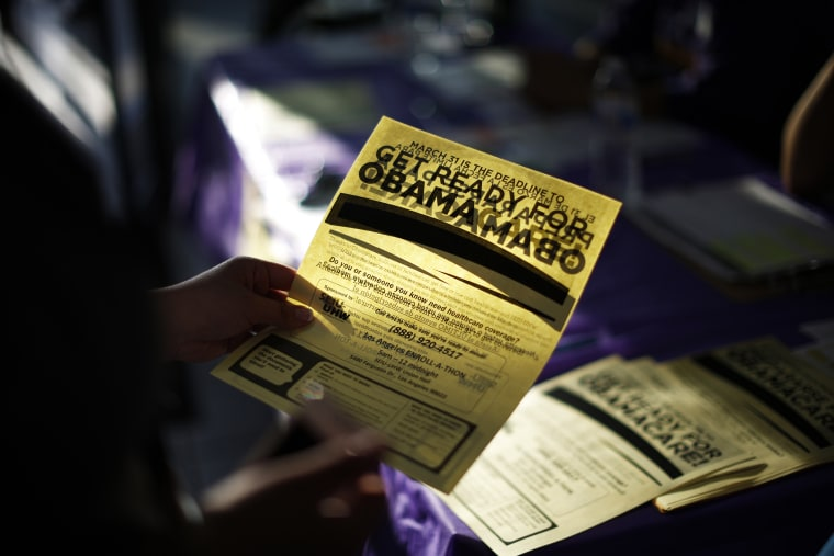 A woman picks up a leaflet at a health insurance enrollment event in Cudahy, Calif., March 27, 2014.