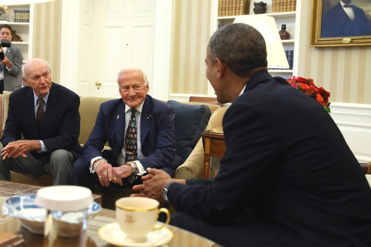 U.S. President Barack Obama (R) meets astronauts Michael Collins (L) and Buzz Aldrin (C) during a visit in the Oval Office at the White House, July 22, 2014 in Washington, DC.