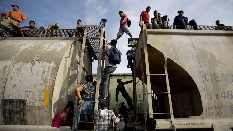 Central American migrants climb on a north bound train during their journey toward the U.S.-Mexico border, in Ixtepec, Mexico, Saturday, July 12, 2014.