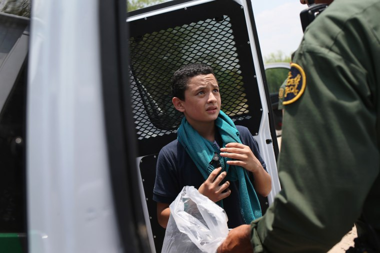 A U.S. Border Patrol agent prepares to take an unaccompanied Salvadorian minor, 13, to a processing center after he crossed the Rio Grande from Mexico into the United States on July 24, 2014 in Mission, Texas.