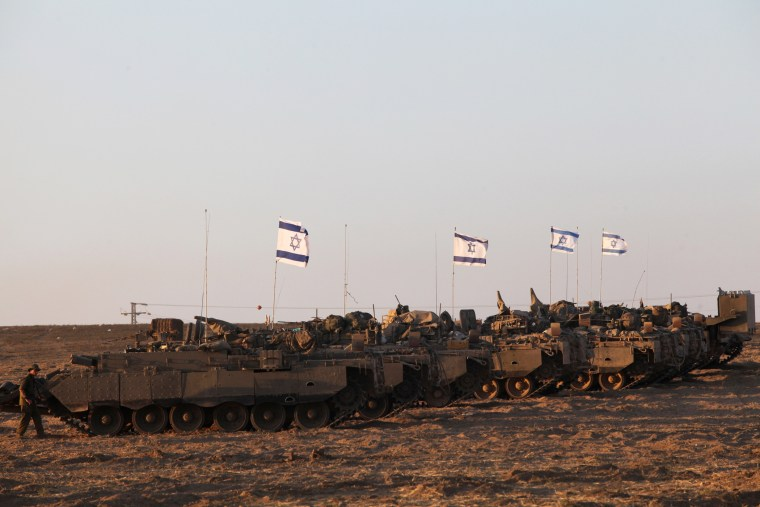 Israeli army's armoured personnel carriers (APC) are positioned along the border between Israel and the Hamas-controlled Gaza Strip on July 26, 2014.