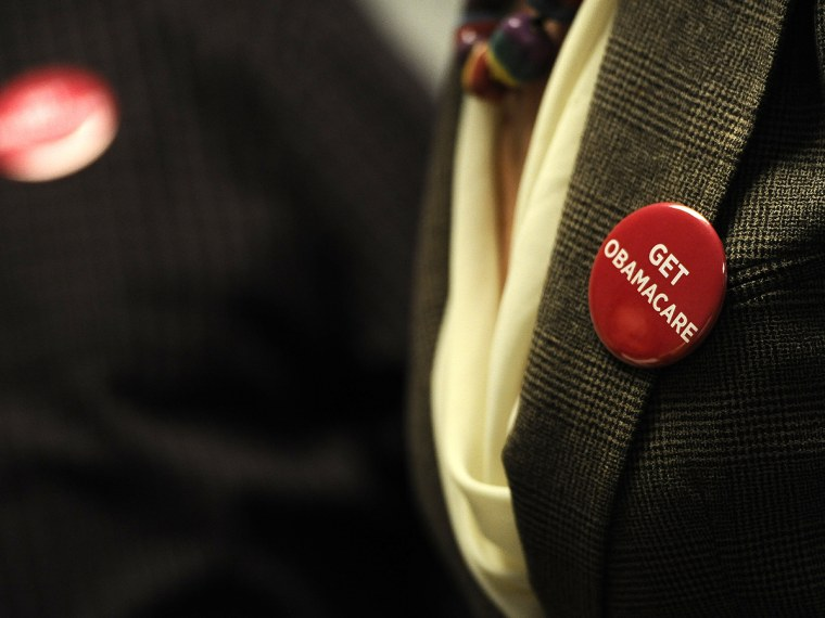 """Associates at Community Health Center wear buttons reading \""""Get Obamacare\"""" during a session to enroll people in the nation's new health insurance system at the Community Health Center, Tuesday, Oct. 1, 2013, in New Britain, Conn."""