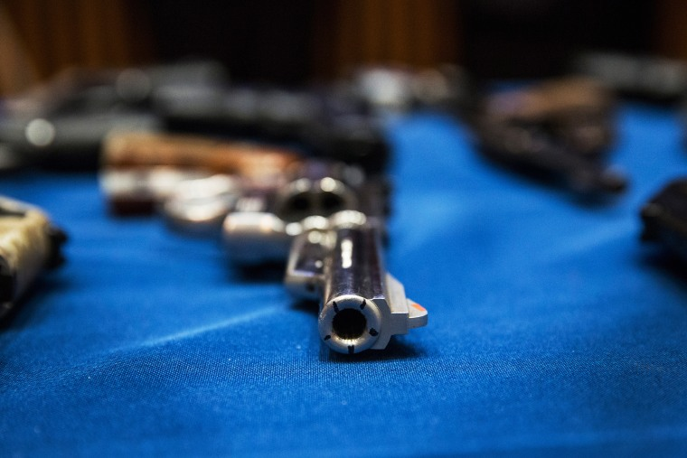 Guns seized by the New York Police Department are displayed during a press conference, August 19, 2013.