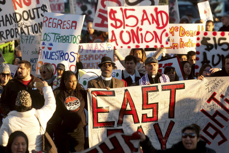 Demonstrators demanding an increase in worker wages march to a Jack in The Box fast food outlet in Oakland
