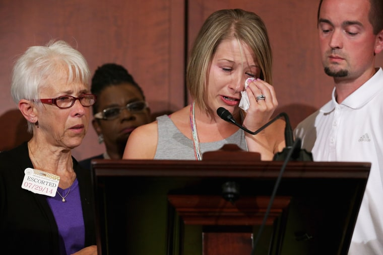 Kacey Mason (C) delivers remarks with her mother Merry Jackson (L), 63, and her husband Dave Mason during a news conference announcing new domestic violence legislation at the U.S. Capitol July 29, 2014 in Washington, DC.