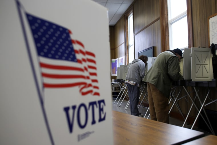A man and woman cast their vote at a polling station on November 6, 2012 in Sugar Creek, Wisconsin.
