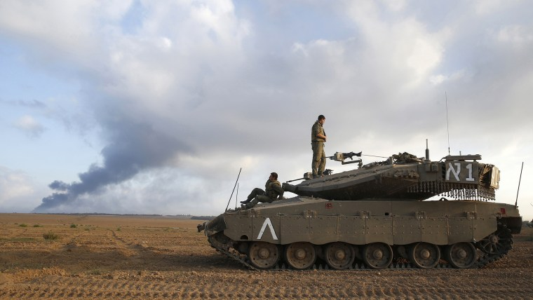 Israeli soldiers are seen atop a tank outside the central Gaza Strip