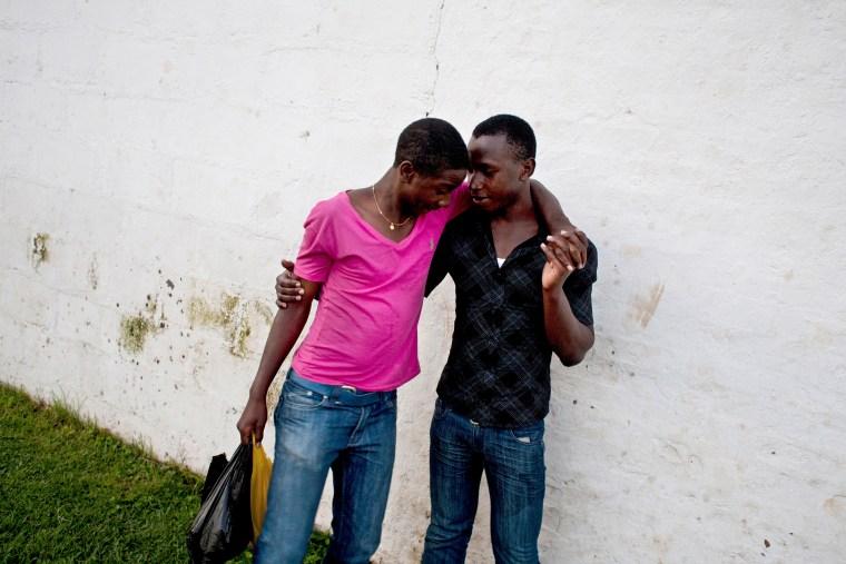Gay couple Kelly and Jonathan walk through a cricket pitch in Kampala, Uganda.