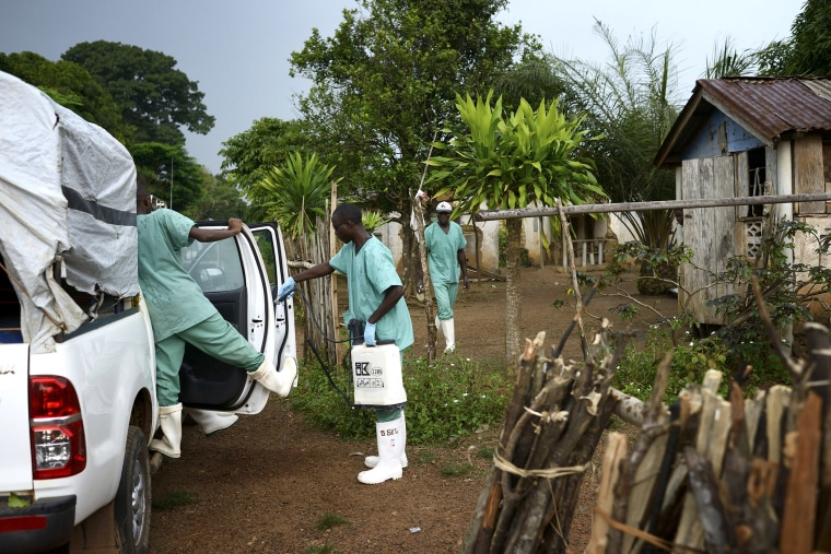 Doctors Without Borders workers wearing protective clothing disinfect materials at a clinic in Teldou, Guinea, July 10, 2014.
