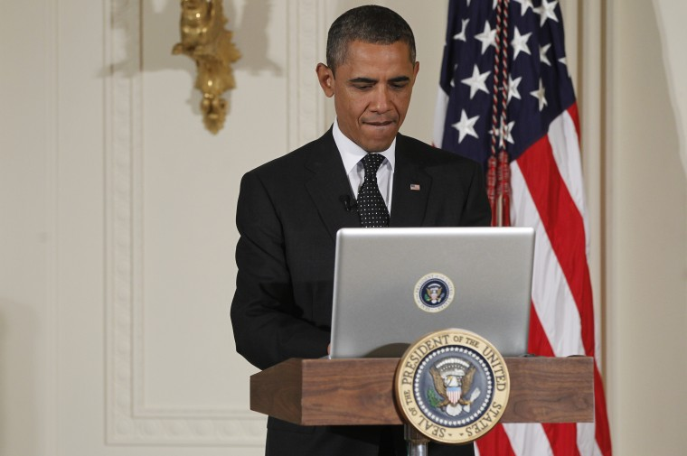 """President Barack Obama uses a laptop computer to send a tweet during a """"Twitter Town Hall"""" in the East Room of the White House in Washington, Wednesday, July 6, 2011."""