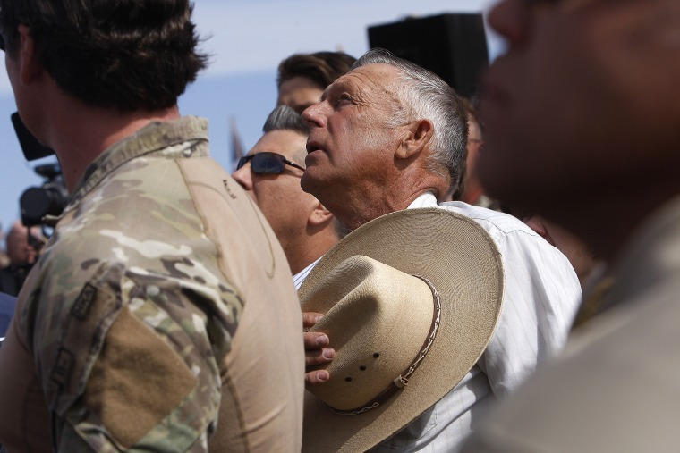 Surrounded by security personnel, rancher Cliven Bundy, middle, sings the National Anthem outside of Bunkerville while gathering with his supporters to challenge the BLM on April 12, 2014.
