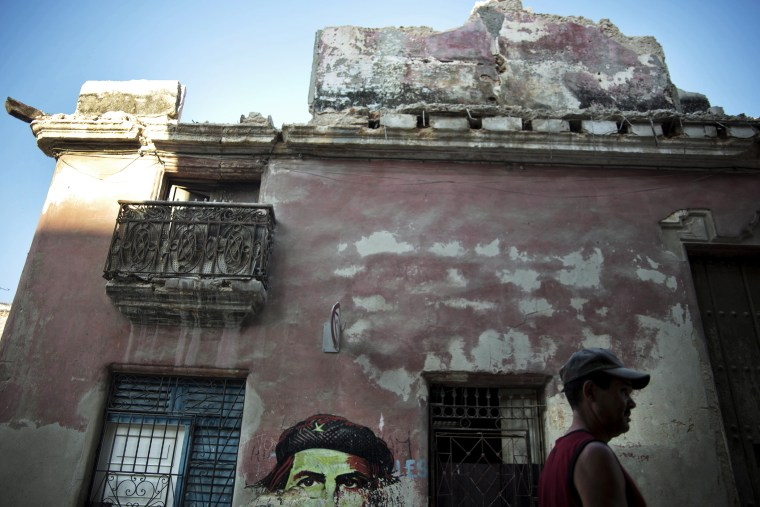 A man walks past a building with an image of revolutionary leader Che Guevara in Havana, Cuba on April 12, 2014.