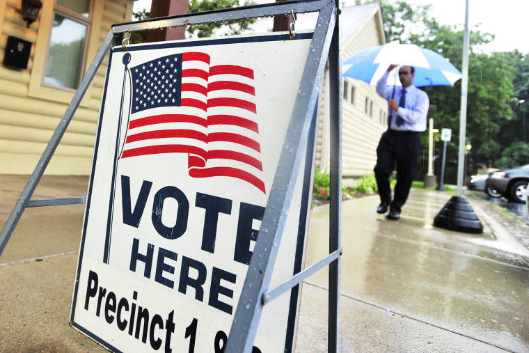 A man walks in the rain to vote at the Rochester Community House in Rochester, Mich. on Tuesday, Aug. 5, 2014.