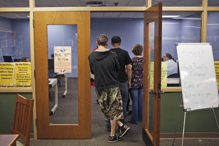 Attendees line up at an Affordable Care Act open enrollment event at a public library in LaGrange, Ky., Oct. 21, 2013.