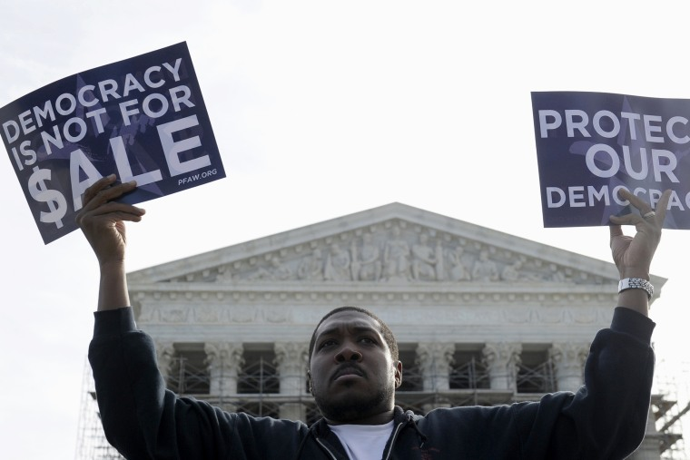 A man takes part in a demonstration outside the Supreme Court in Washington as the court heard arguments on campaign finance, Oct. 8, 2013.