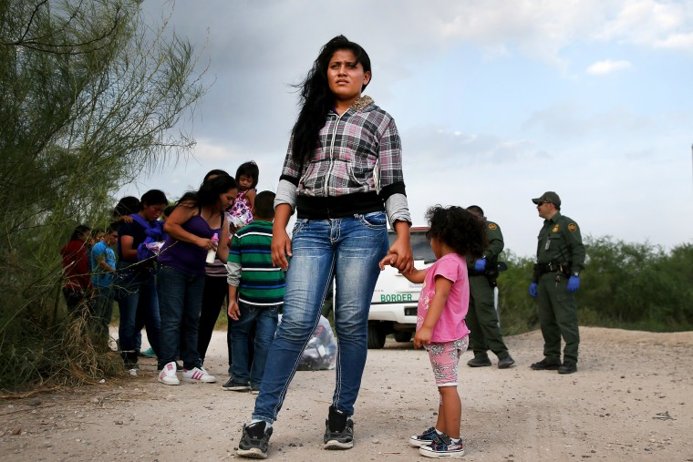 Honduran immigrants wait as a Border Patrol vehicle arrives to transport their group to a processing center, July 24, 2014 in Mission, Texas.