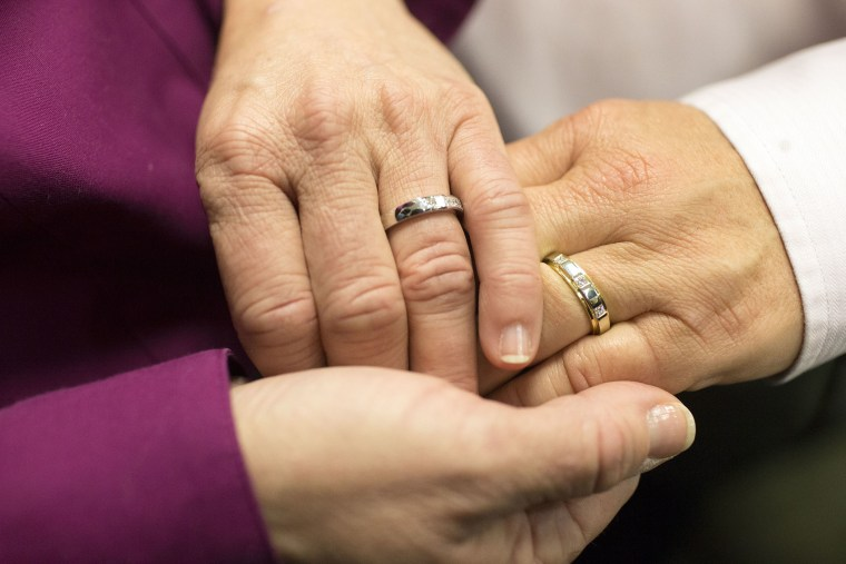Jonnie Terry joins hands with her partner of 28 years, Elizabeth Patten, during their marriage ceremony at the Washtenaw County Clerk's Office in Ann Arbor, Mich., March 22, 2014.