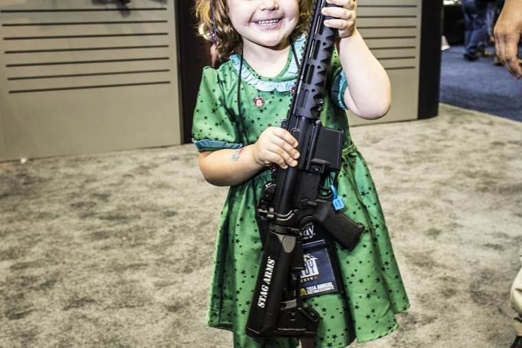 A four year old girl poses for a photo with an assault rifle at the NRA's annual convention in Indianapolis, Indiana, April 2014.