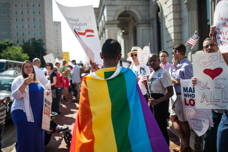 A same-sex marriage supporter wears a rainbow cape behind 4th U.S. Circuit Court of Appeals after a court hearing on May 13, 2014 in Richmond, Va.