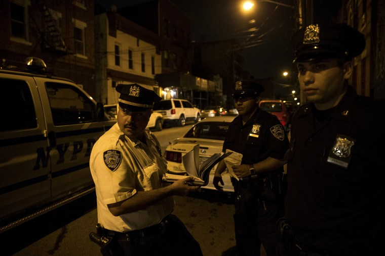 Police officers on scooters watch children playing at night outside a housing project in the Brooklyn borough of New York.