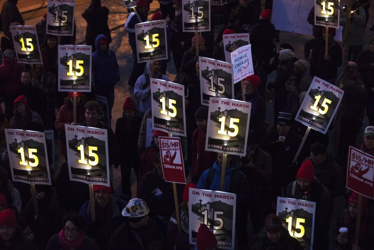 Demonstrators stage a rally to raise the hourly minimum wage to $15 for fast-food workers at City Hall in Seattle, Washington, Dec. 5, 2013.