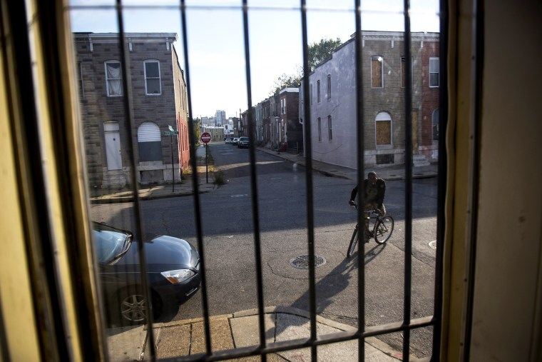 A resident rides his bike in an abandoned block in East Baltimore, Oct. 28, 2013.