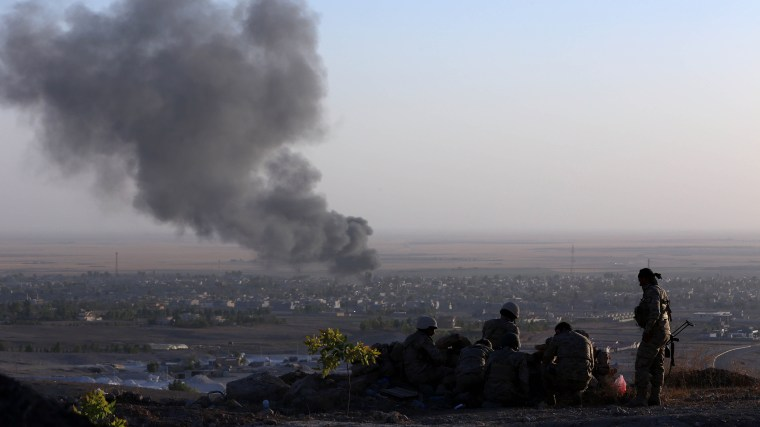 Iraqi Kurdish Peshmerga fighters look on as smoke billows from the town Makhmur, about 280 kilometres (175 miles) north of the capital Baghdad, during clashes with Islamic State (IS) militants on Aug. 9, 2014.