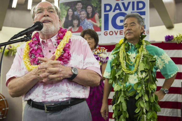 Hawaii Governor Neil Abercrombie, left, addresses the supporters of Hawaii State Sen. David Ige as Ige, right, looks, Aug. 9, 2014, in Honolulu, Hawaii.