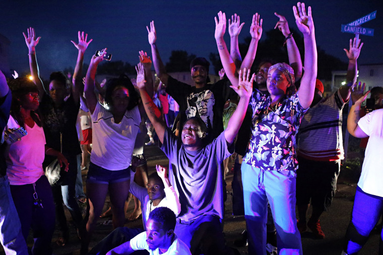 """Don't shoot us'' cries out the crowd as they confront police officers arriving to break up a crowd in Ferguson, Mo., Aug. 9, 2014."