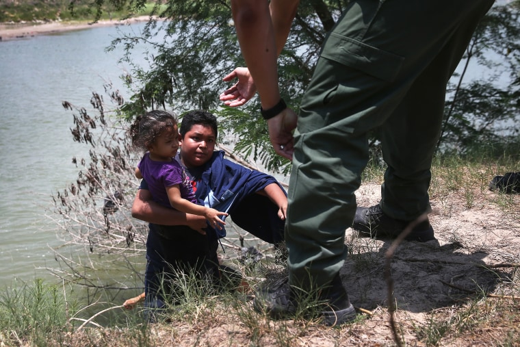 A U.S. Border Patrol agent assists undocumented minors after they crossed the Rio Grande from Mexico into the United States on July 24, 2014 in Mission, Texas.