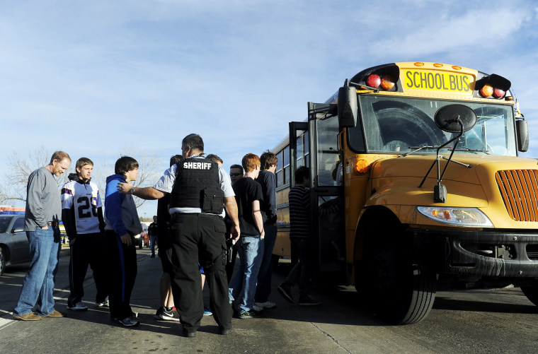 A Douglas County Sheriff's Deputy helps students to board a bus after a school shooting on December 13, 2013 at Arapahoe High School in Centennial, Colorado.