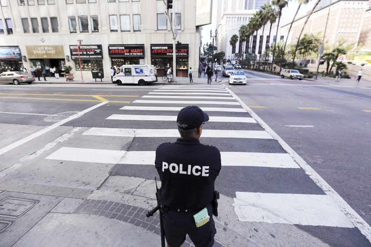 An LAPD officer watches a downtown intersection in Los Angeles, Calif., Dec. 17, 2013.