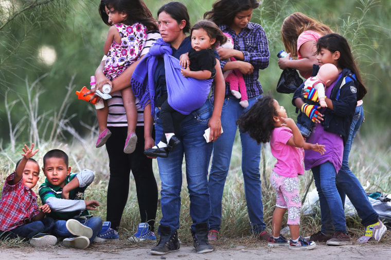 Central American immigrants await transportation to a U.S. Border Patrol processing center after crossing the Rio Grande from Mexico into the Texas on July 24, 2014 near Mission, Texas.