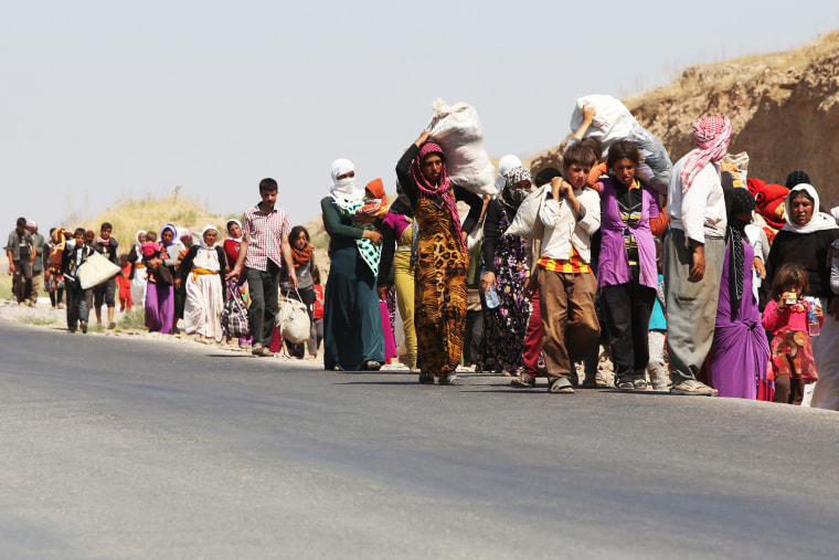 Displaced Iraqi families from the Yazidi community cross the Iraqi-Syrian border at the Fishkhabur crossing, in northern Iraq, on August 13, 2014.