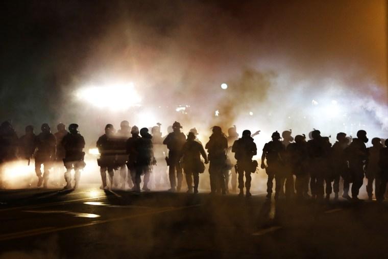 Police advance through smoke, Wednesday, Aug. 13, 2014, in Ferguson, Mo.