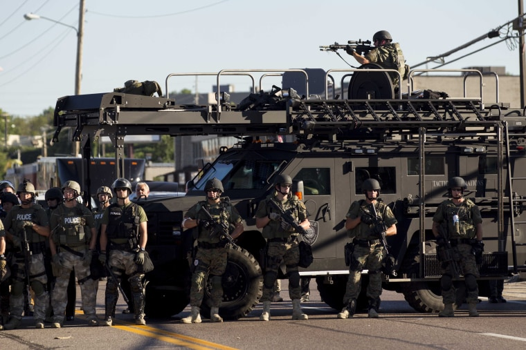 Law enforcement officers, including a sniper perched atop an armored vehicle, watch as demonstrators protest the fatal shooting of Michael Brown, in Ferguson, Mo.