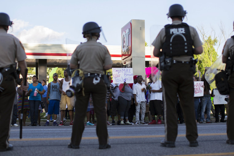 Police officers watch as demonstrators protest the death of black teenager Michael Brown in Ferguson, Missouri Aug. 12, 2014.