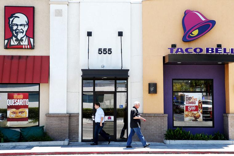 Pedestrians walk by a KFC and a Taco Bell restaurant on July 2, 2014 in San Rafael, California.