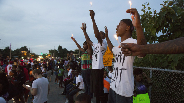 People hold candles during a peaceful demonstration, as communities react to the shooting of Michael Brown in Ferguson, Missouri August 14, 2014.