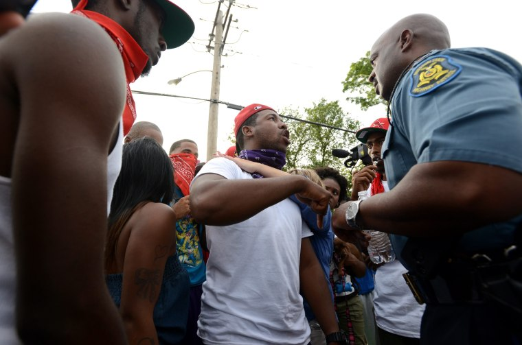 Captain Ron Johnson, of the Missouri State Highway Patrol (R) listens to protesters complaints about the death of Michael Brown across the street from a burned down Quik Trip gas station on West Florissant Avenue in Ferguson, Missouri, August 14, 2014.