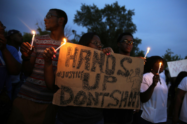 Demonstrators hold candles and signs, Aug. 14, 2014, in Ferguson, Mo.