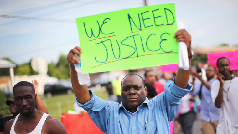 Demonstrators protest the shooting death of teenager Michael Brown on August 14, 2014 in Ferguson, Missouri.